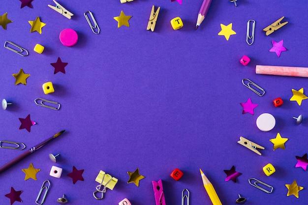 Rifornimenti di scuola multicolori su fondo viola con lo spazio della copia.