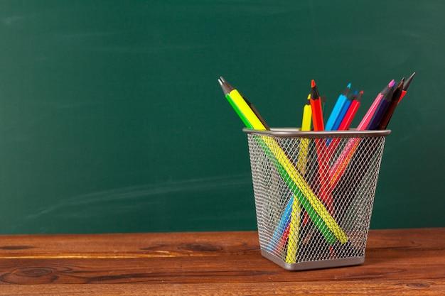 Rifornimenti di scuola su una tavola di legno e su un fondo della lavagna