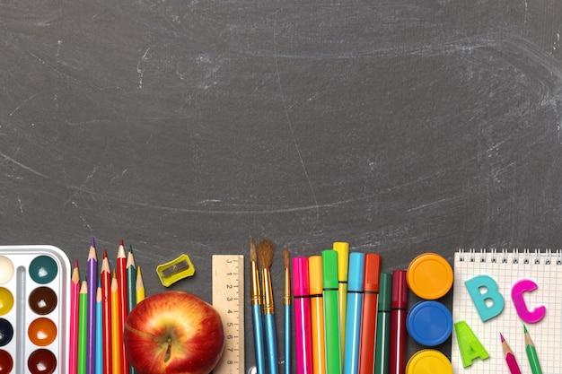 Rifornimenti di scuola sulla priorità bassa nera della lavagna.