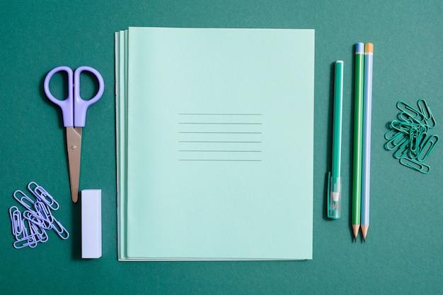 Rifornimenti di scuola, taccuino, penna e matita su uno sfondo verde.