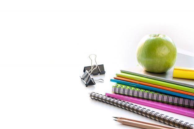Rifornimenti di scuola variopinti, libro, mela su bianco. avvicinamento. di nuovo a scuola.
