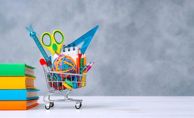 Rifornimenti di scuola variopinti nel cestino della spesa su un fondo grigio con una copia dello spazio del testo. una pila di libri con copertine colorate. il concetto di tornare a scuola per il nuovo anno accademico.