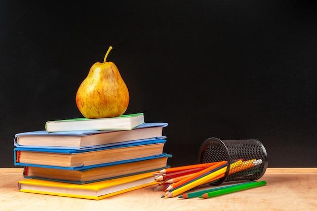 Rifornimenti, libri e pera di scuola differenti sulla tavola di legno