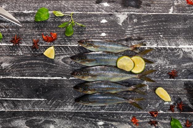 Riga del pesce su fondo di legno nero, concetto che cucina fondo