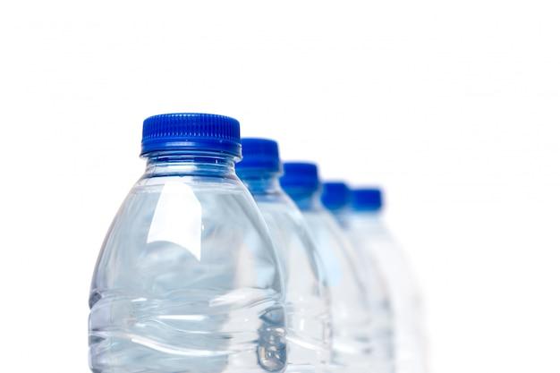 Riga delle bottiglie di acqua di plastica isolate su una priorità bassa bianca.