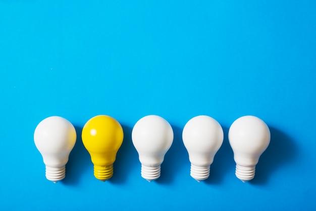 Riga delle lampadine bianche con la lampadina gialla su priorità bassa blu