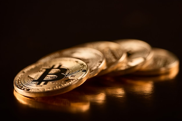 Riga di bitcoins dorati brillanti come valuta digitale principale al giorno d'oggi isolata su fondo nero.