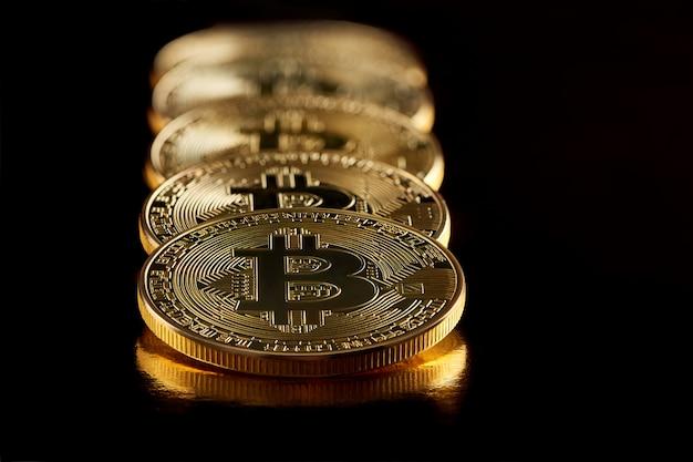 Riga di bitcoins dorati che rappresentano le criptovalute principali al giorno d'oggi isolate su fondo nero.