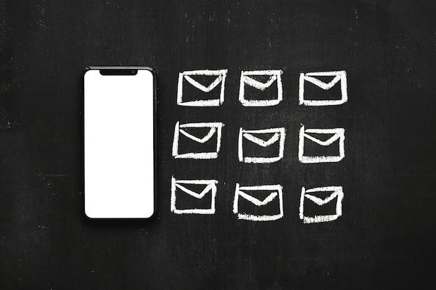 Riga di icona piccoli messaggi disegnati vicino al cellulare sulla lavagna