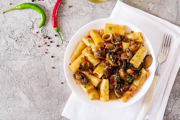 Rigatoni di pasta vegetariana con funghi e peperoncino in ciotola bianca