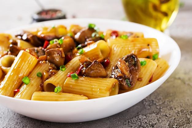 Rigatoni vegetariani della pasta con i funghi e i peperoncini in ciotola bianca sulla tavola grigia. cibo vegano.