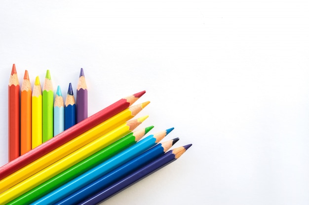 Righe delle matite di colore sulla priorità bassa del libro bianco, spazio della copia. articoli per ufficio, ritorno a scuola.