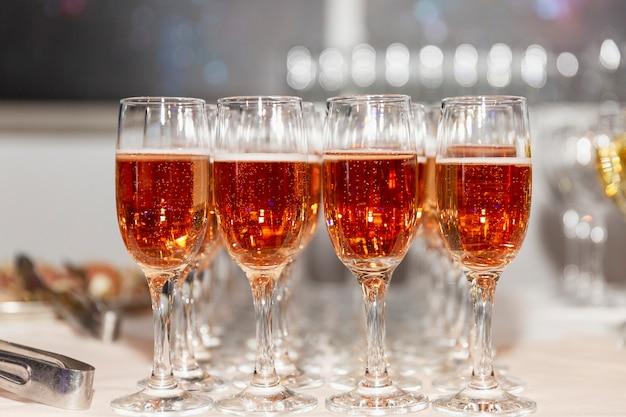 Righe di bicchieri con champagne rosa su un tavolo da buffet festivo. esci dalla registrazione degli eventi.