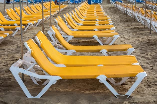 Righe di lettini gialli sulla spiaggia di playa de puerto rico sull'isola delle canarie