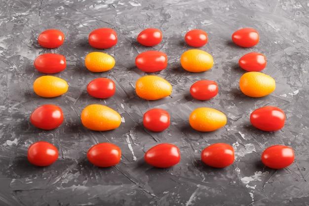Righe di pomodorini e kumquat, concetto di contrasto.