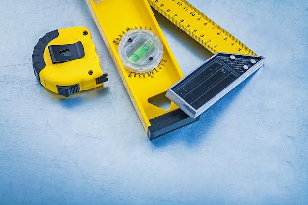 Righello di misurazione giallo del livello della costruzione del nastro e quadrato sul concetto metallico di manutenzione del fondo
