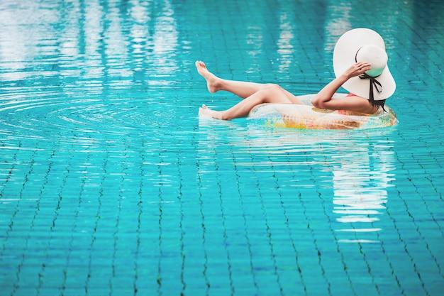 Rilassamento della donna del bikini sul galleggiante dello stagno