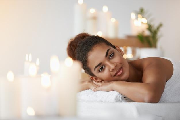 Rilassamento di riposo sorridente della bella donna africana nel salone della stazione termale.