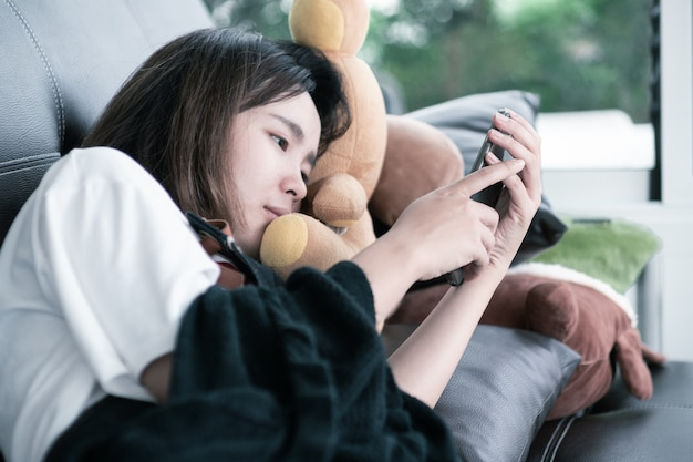 Rilassamento sul sofà donna adulta che tiene telefono cellulare e messaggio di chiacchierata