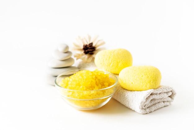 Rilassante composizione di prodotti da bagno con bombe da bagno a forma di cuore giallo, rottami di sale marino, fiori, asciugamano e catasta di pietre