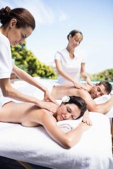 Rilassata giovane coppia riceve un massaggio alla schiena da massaggiatore in una spa