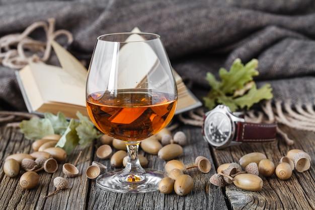 Rilassati con l'alcol. quercia autunnale e bicchiere di whisky
