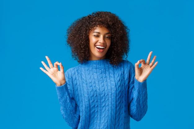 Rilassati e rilassati, tutto bene. la giovane donna afroamericana spensierata bella allegra che mostra la calma, gesto giusto, assicura tutto bene e sorridendo, stando blu soddisfatto