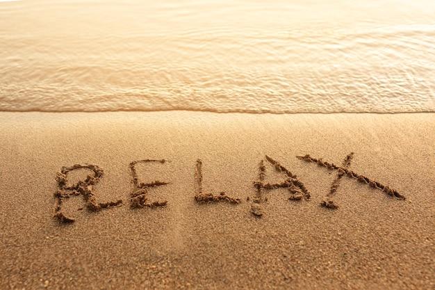 Rilassati scritto sulla sabbia