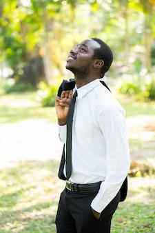 Rilassi l'uomo d'affari africano togliersi il vestito con il verde naturale.