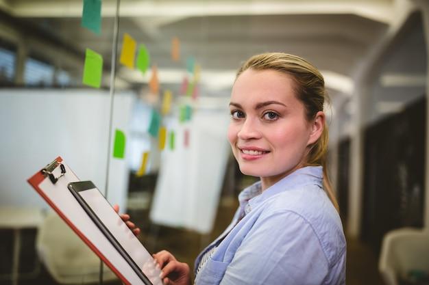 Rilievo di nota della holding della donna di affari e compressa digitale in ufficio creativo