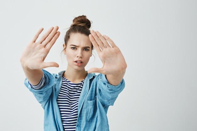 Rimani fermo mentre ti faccio una foto. ritratto della ragazza messa a fuoco e seria con l'acconciatura del panino che tira le mani verso la macchina fotografica che prova a trovare l'angolo retto per iniziare a disegnare