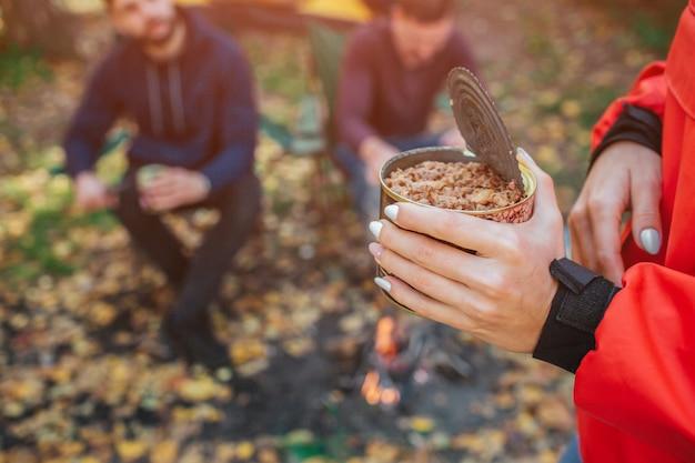 Rimorchia i giovani che si siedono nella sedia pieghevole dietro. giovane donna tenere in mano cibo cneed. sono nella foresta.