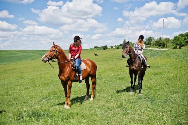 Rimorchia le giovani ragazze graziose che guidano cavalli su un campo al giorno soleggiato