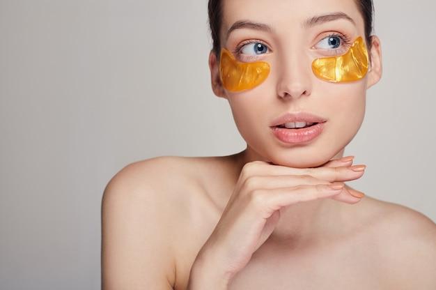 Rimozione di rughe e occhiaie. una donna si prende cura della pelle delicata intorno agli occhi. procedure cosmetiche. cura della pelle del viso