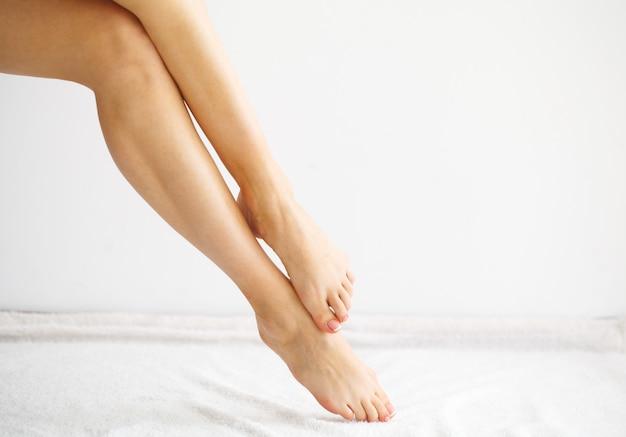 Rimozione peli. chiuda sulle mani della donna che toccano le gambe lunghe, pelle morbida