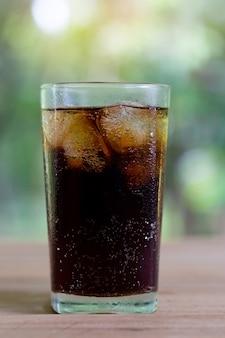 Rinfrescanti bevande analcoliche di soda o cola con ghiaccio in un bicchiere alto chiaro con lo sfondo della natura.