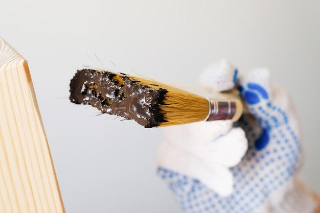 Riparatore, carpentiere, gran lavoratore applica una vernice protettiva o vernice su una tavola di legno.