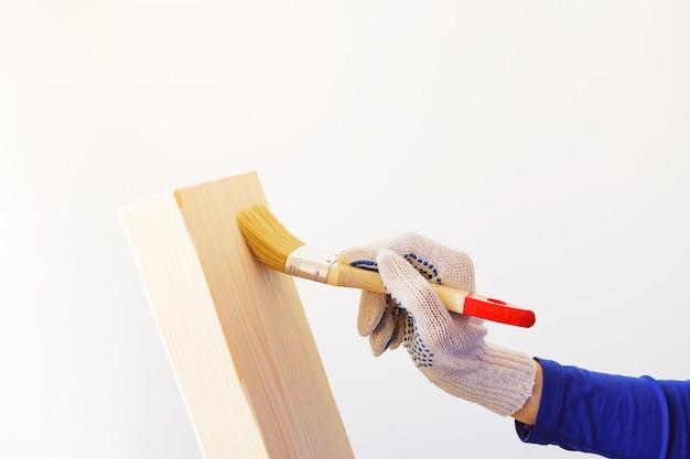 Riparatore, carpentiere, gran lavoratore applicare una vernice protettiva con un pennello su una tavola di legno.