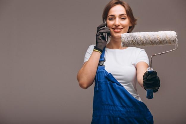 Riparatore della donna con il rullo di pittura isolato parlando al telefono