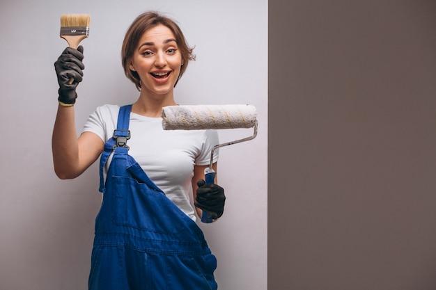 Riparatore della donna con il rullo di pittura isolato