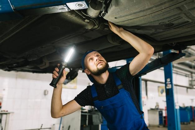 Riparatori che ispezionano la trasmissione dell'automobile