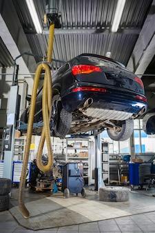 Riparazione auto su un ascensore per la riparazione del telaio, cambio automatico e motore nell'officina riparazioni auto o garage.