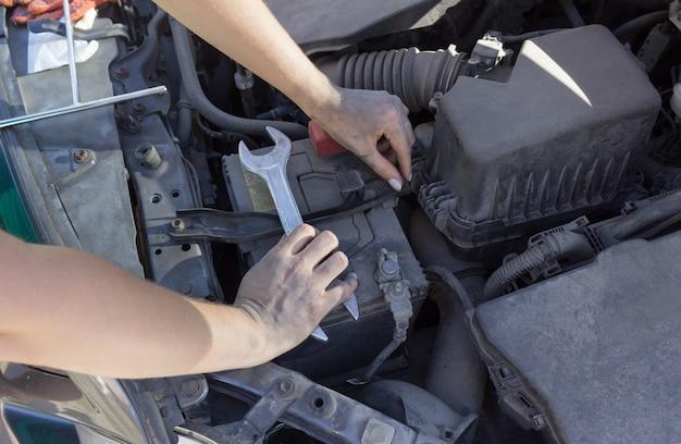 Riparazione batteria auto sotto il cofano, riparazione auto mani femminili