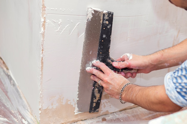 Riparazione degli alloggi. stucco pareti interne con un'ampia spatola metallica