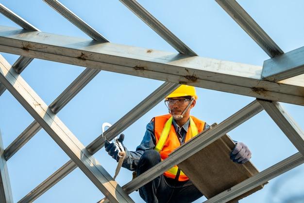Riparazione del tetto, muratore che usando la pistola del chiodo per installare il nuovo tetto sul tetto superiore, concetto in costruzione dell'edificio residenziale