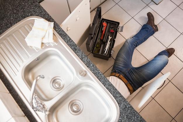 Riparazione dell'idraulico sotto il lavandino