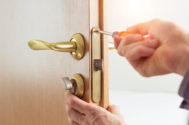 Ripari la serratura della porta. installazione della maniglia della porta.