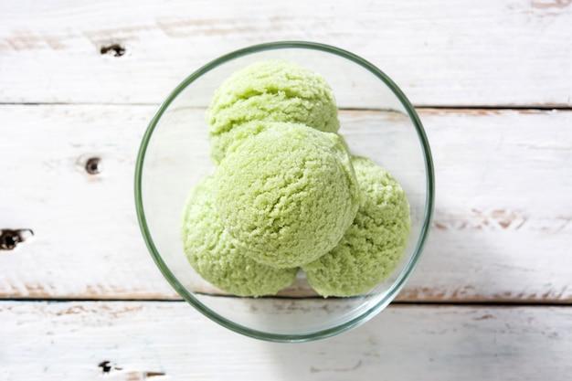 Ripartitori di matcha del tè verde in ciotola a cristallo sulla vista di legno bianca del piano d'appoggio