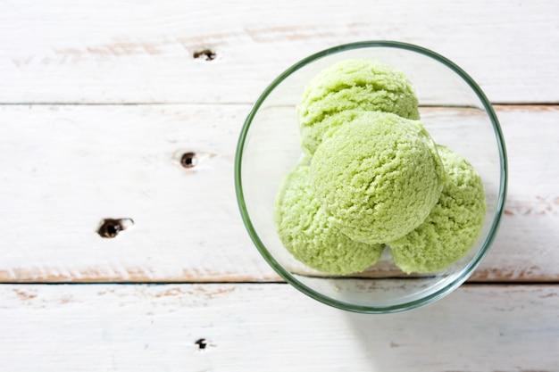 Ripartitori di matcha del tè verde in ciotola a cristallo sullo spazio di legno bianco della copia di vista del piano d'appoggio