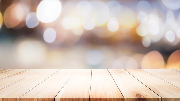 Ripiano del tavolo di legno sulle luci del bokeh